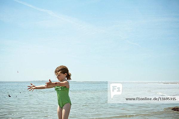 Mädchen spielt mit Sand am Strand