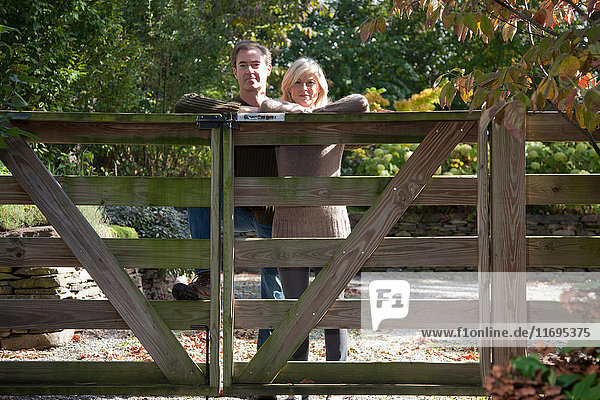 Couple leaning on wooden gate