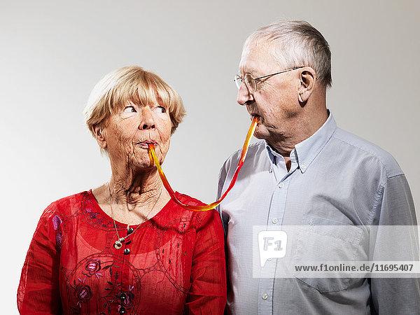Älteres Ehepaar teilt sich Süßigkeiten vor weißem Hintergrund