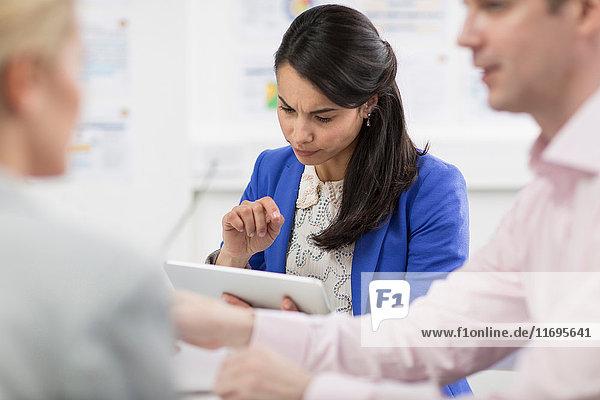 Geschäftsfrau verwendet digitales Tablet in Besprechung