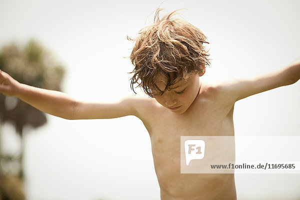 Bare-chested boy playing outdoors