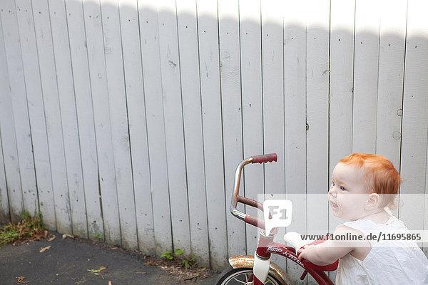 Mädchen schiebt Dreirad