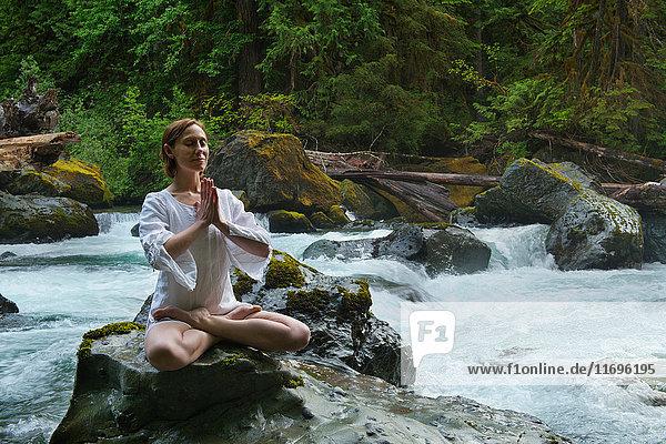 Frau meditiert auf Felsen am Wasser