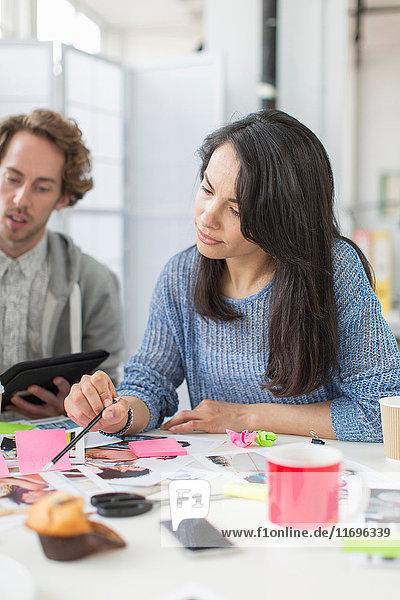 Mittlere erwachsene Frau bespricht Pläne in Kreativbüro-Sitzung