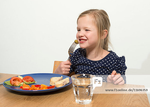 Smiling girl eating at table