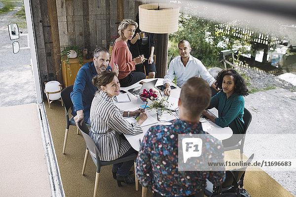 Blickwinkel von Geschäftsleuten  die in einem tragbaren Bürotruck diskutieren