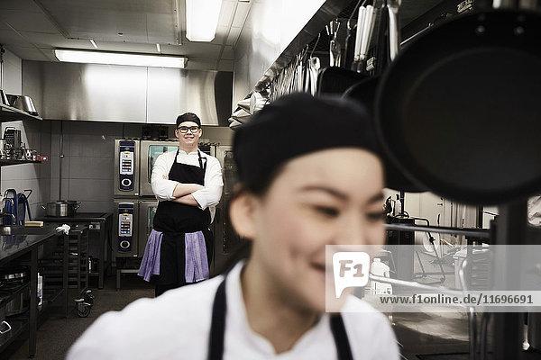 Porträt des selbstbewussten Küchenchefs mit Kollege im Vordergrund in der Großküche