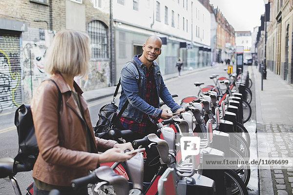Ein multiethnisches Paar  das Fahrräder vom Fahrradstand in der Stadt leiht.