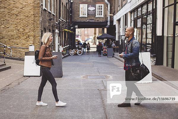 Durchgehende Seitenansicht des Paares  das auf der Straße in der Stadt aufeinander zugeht.