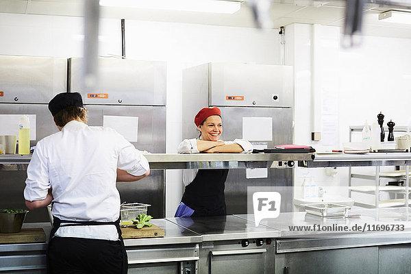 Lächelnde Köchin  die sich auf den Tresen stützt  mit Schülerin  die in der Kochschule arbeitet
