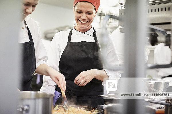 Lehrerin beobachtet Kochstudentin beim Kochen in der Küche im Restaurant