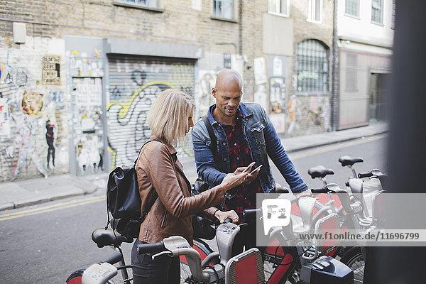 Paar mit Mobiltelefonen am Fahrrad-Sharing-System