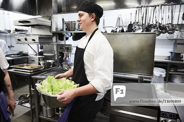 Seitenansicht des männlichen Kochstudenten mit Gemüsebehälter in der Großküche
