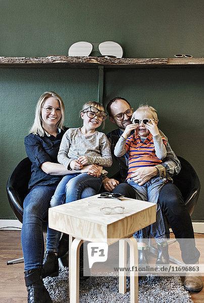 Volle Länge der glücklichen Familie in der Brillenwerkstatt