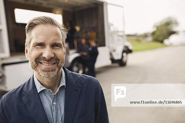 Portrait eines glücklichen Geschäftsmannes auf der Straße mit Kollegen und tragbarem Bürowagen im Hintergrund