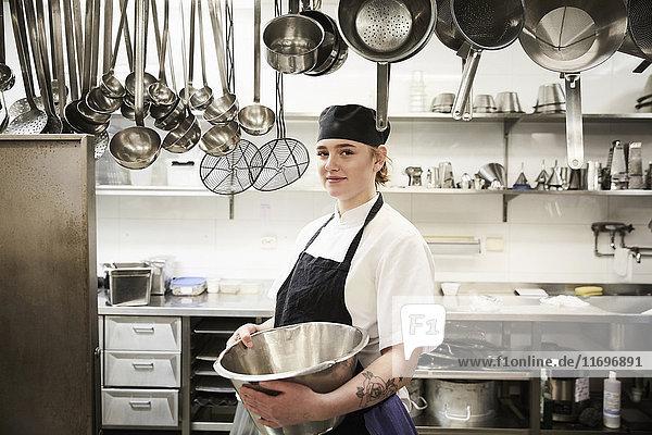 Porträt einer selbstbewussten Köchin mit Container in der Großküche