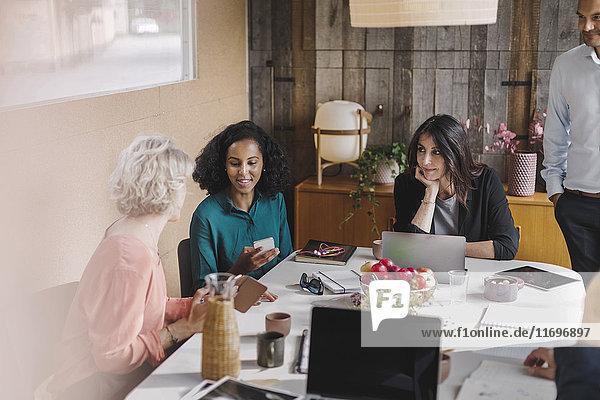 Geschäftsfrau  die während der Besprechung in einem tragbaren Bürowagen Kollegen mit Mobiltelefonen ansieht.