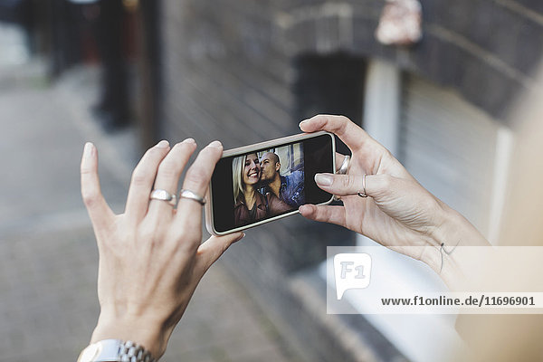 Mann küsst Frau  wie sie Selfie durch Smartphone nimmt