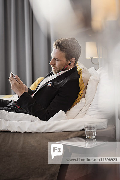 Side view of mature businessman using mobile phone while lying on bed at hotel room