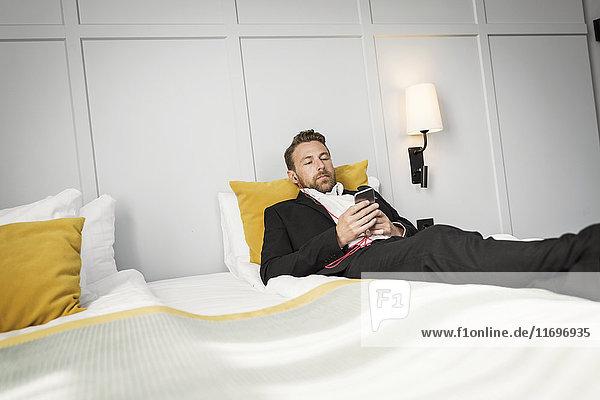 Geschäftsmann liegt auf dem Bett und hört Musik vom Handy im Hotelzimmer.