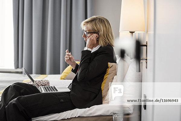 Seitenansicht der Geschäftsfrau beim Einstellen der Kopfhörer mit Laptop im Hotelzimmer