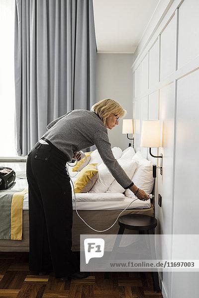 Geschäftsfrau  die das Kabel am Bett im Hotelzimmer anschließt.