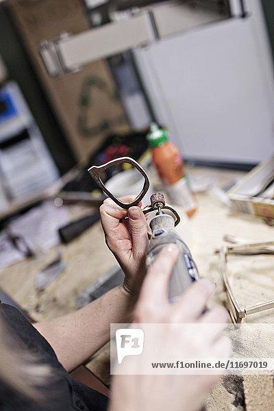 Abgeschnittenes Bild der Brillenmacherin mit Arbeitsgerät in der Werkstatt