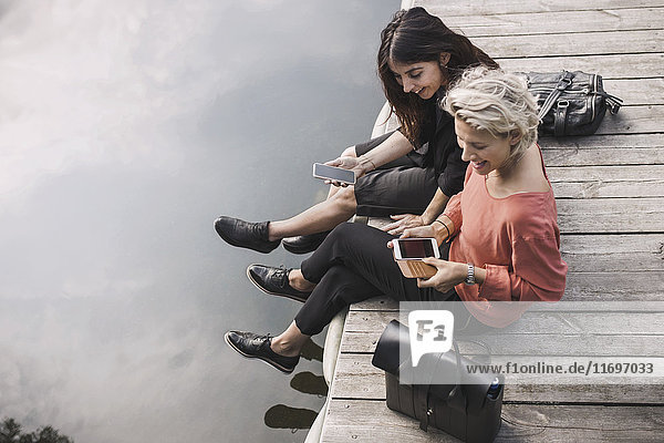 Großer Blickwinkel auf glückliche Geschäftsfrauen mit dem Smartphone auf dem Pier am See