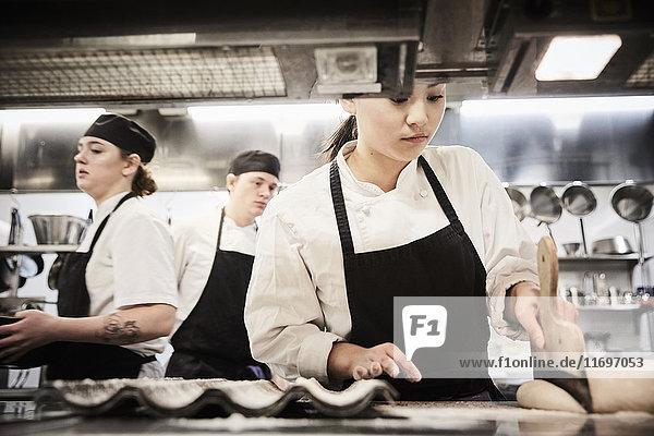 Kochstudentin beim Teigschneiden in der Großküche