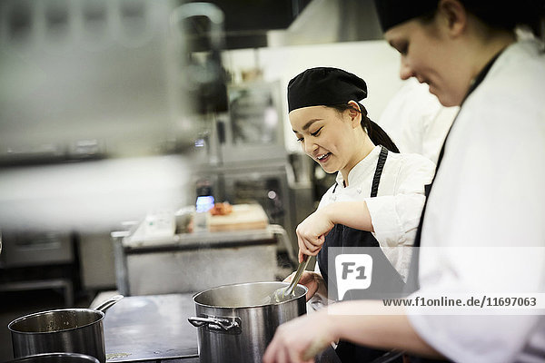 Female chef student with colleague cooking food in commercial kitchen