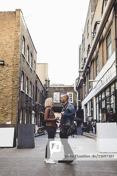 Seitenansicht des Paares  das auf der Straße in der Stadt spricht.