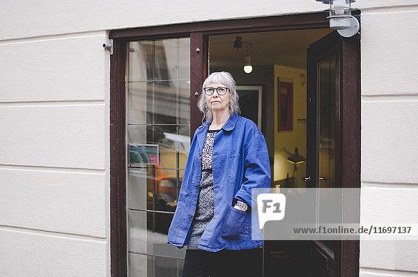 Senior Besitzerin stehend mit Händen in Taschen außerhalb des Juweliergeschäftes