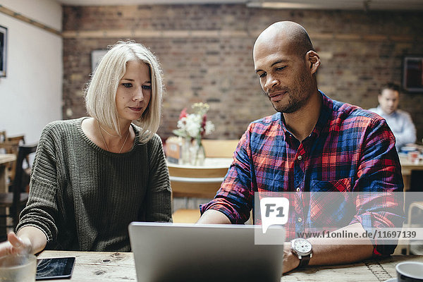 Couple using laptop at table in coffee shop