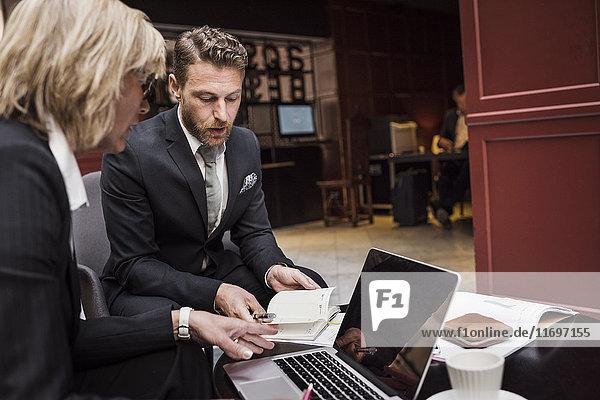 Geschäftsleute besprechen Vertrag in der Hotelrezeption