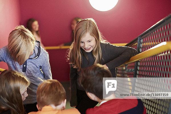 Lächelndes Mädchen mit Freunden auf der Treppe der Mittelschule