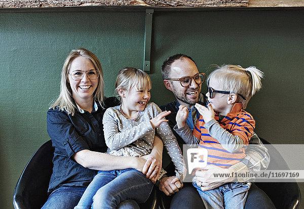 Glückliche Familie in der Brillenwerkstatt