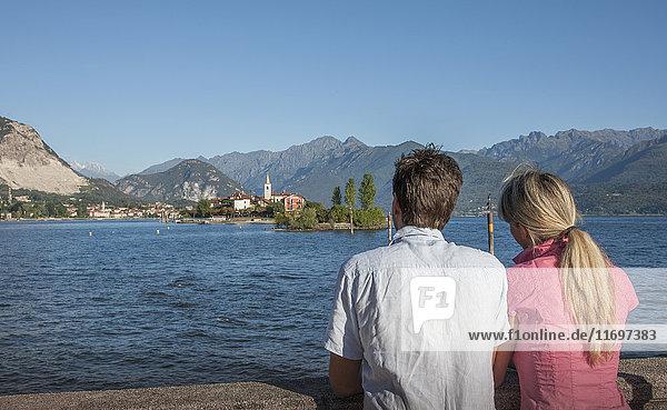 Caucasian couple admiring scenic view of lake
