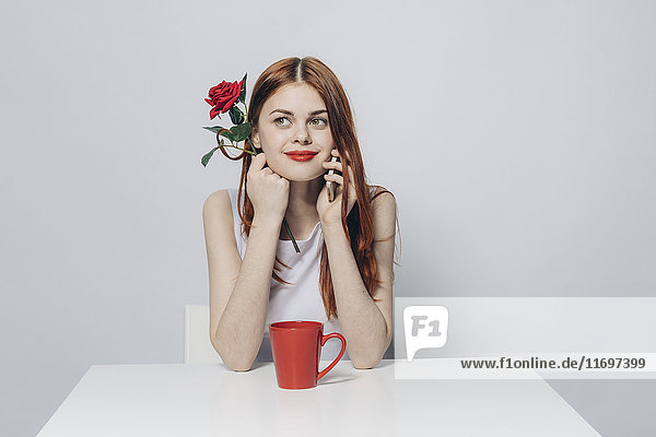 Caucasian woman sitting at table holding rose talking on cell phone