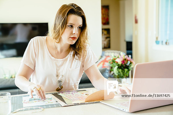 Woman sitting at table making bow and using laptop