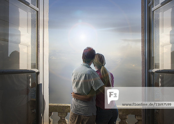 Caucasian couple admiring scenic view of lake from balcony