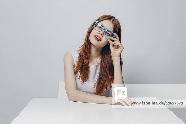 Pensive Caucasian woman sitting at table wearing blue eyeglasses