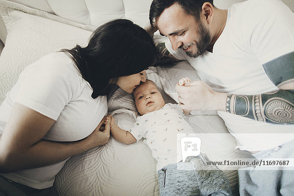 Caucasian mother and father holding hands with baby son on bed