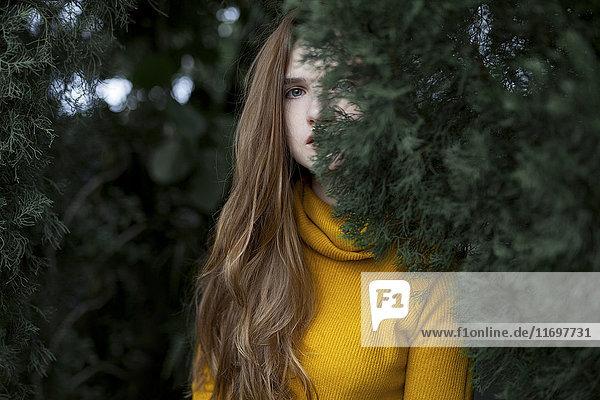 Serious Caucasian woman hiding behind tree
