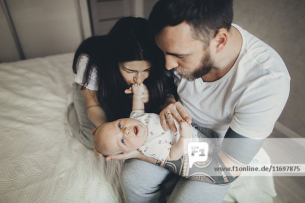 Caucasian mother and father on bed playing with baby son