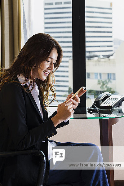 Smiling Thai businesswoman texting on cell phone in office