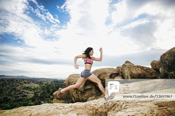 Hispanic woman running on rock formation