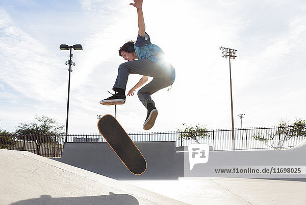 Hispanic man performing mid-air trick on skateboard