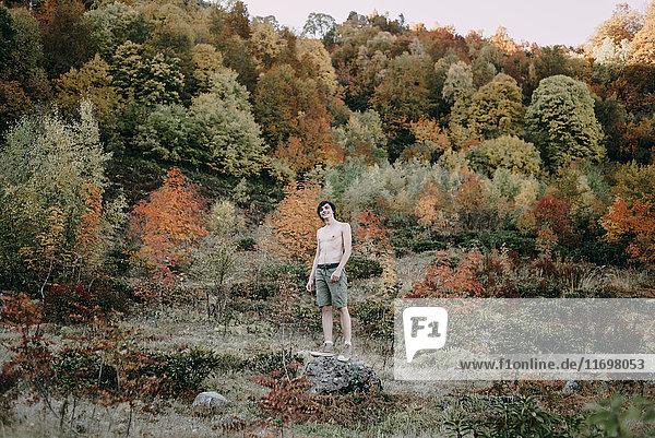 Caucasian man standing on rock in autumn