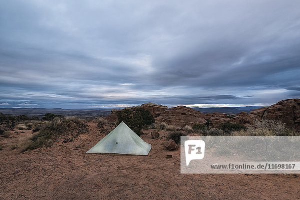 Camping tent in landscape under clouds