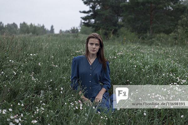 Serious Caucasian teenage girl sitting in field of wildflowers